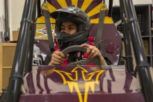 Mikayla Castillo, Freshman studying Mechanical Engineering, demonstrates how to get out of Sun Devil Racing's buggie