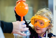 Annabeth Shown learns how to fill a balloon with gas in the Fun with Chemistry room during the Open Door at Polytechnic Campus in Mesa, Ariz. on Friday evening January 26th, 2018.