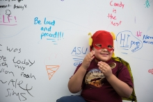 """Nathaniel Garcia poses for a photo with his ice cream """"sweet tweet,"""" on the wall at the Communication Assessment & Learning Lab during Open Door at West Campus on Saturday Feb. 10th, 2018 in Glendale, Ariz."""